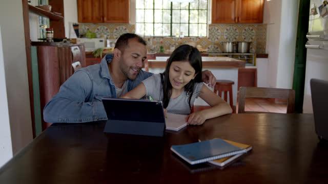 vídeos y material grabado en eventos de stock de padre amoroso ayudando a su hija durante la clase explicando algo que apunta a la tableta - encierro covid-19 - padre soltero