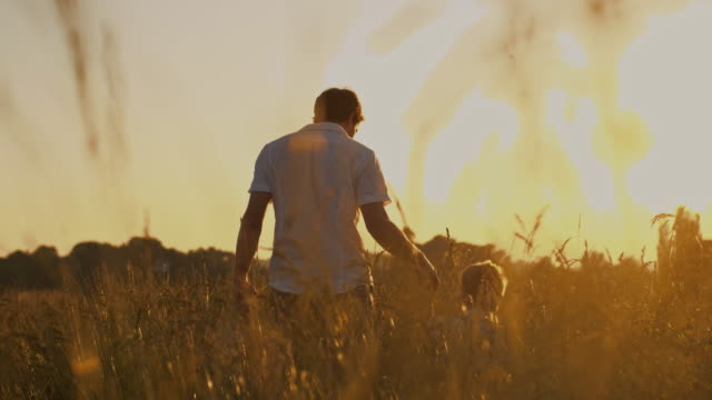 SLO MO Loving father holding son's hand in grass