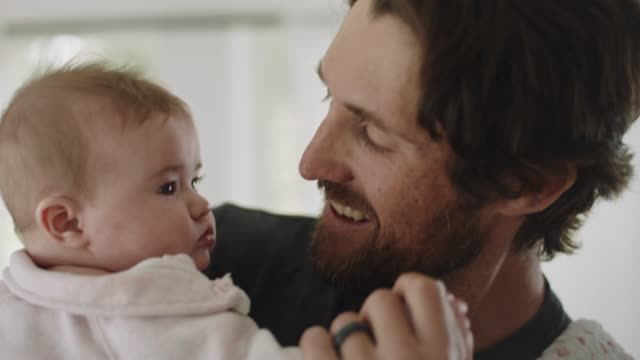 vídeos de stock e filmes b-roll de cu slo mo. loving father holds infant daughter's hand and dances with her in sunny living room. - papa