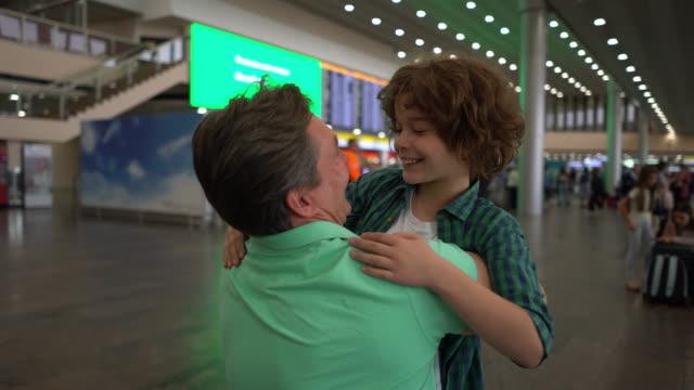vídeos y material grabado en eventos de stock de padre amoroso abrazando y hablando con su hijo mientras acababa de aterrizar en el aeropuerto - saludar