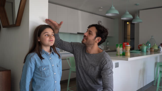 loving father measuring daughter with excitement against the wall both celebrating her growth - high up stock videos & royalty-free footage