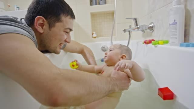 vídeos de stock e filmes b-roll de loving father playing with his son during bathtime - banheira