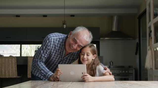 liebender großvater, der auf enkelin schaut, während sie auf dem tablet spielt - großvater stock-videos und b-roll-filmmaterial