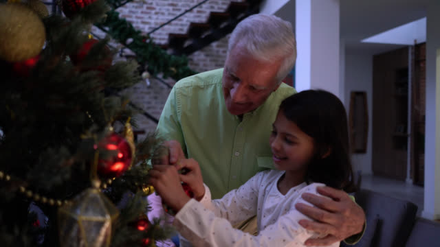 loving grandfather decorating with granddaughter the christmas tree hugging and smiling - tree hugging stock videos & royalty-free footage