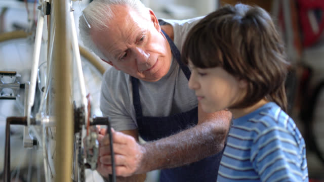 Liefdevolle grootvader zijn kleinzoon onderwijzen hoe te doen van onderhoud op een fiets