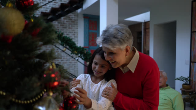 loving grandmother and little girl decorating the christmas tree together hugging and smiling - tree hugging stock videos & royalty-free footage