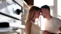 A loving happy couple is kissing, hugging and drinking coffee in the sunny kitchen