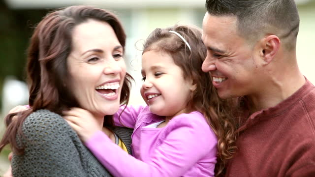 loving hispanic family with little girl, hugs and kisses - two parents stock videos & royalty-free footage