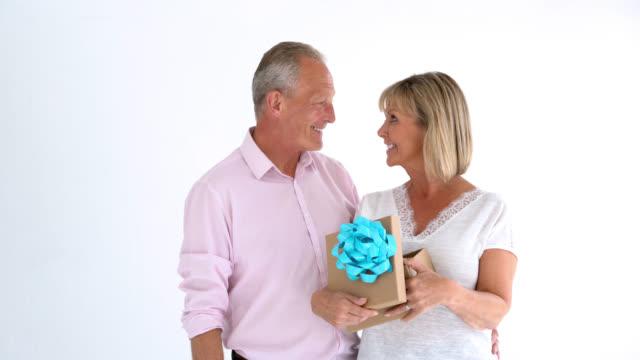 vídeos de stock e filmes b-roll de loving husband surprising his wife with a gift for anniversary - carinhoso