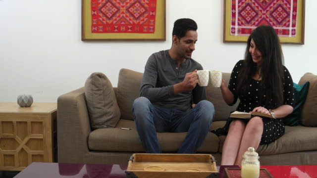 loving indian couple in a living room sharing ideas, thoughts and coffee - indian couple tea stock videos & royalty-free footage