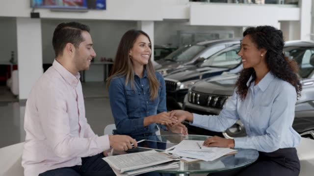 vídeos de stock, filmes e b-roll de casal latino-americano amando fechar um negócio em um carro assinando um contrato na concessionária com vendedora negra amigável - vender