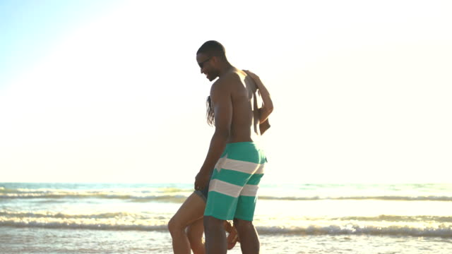 Loving man carrying woman on shore against sky