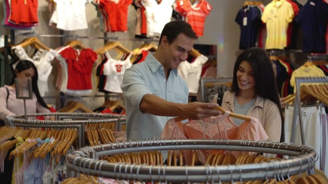 loving man choosing a blouse for partner while both are talking and smiling - grande magazzino video stock e b–roll