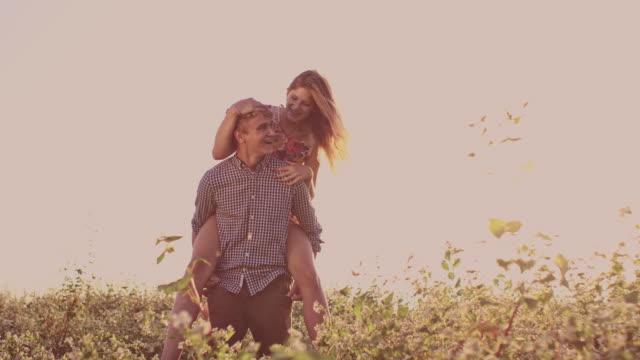 SLO MO Loving man giving his girlfriend a piggyback