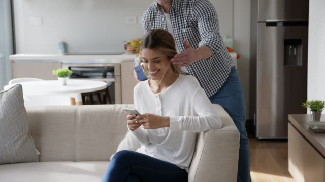 loving man surprising his girlfriend with a gift while she is texting on smartphone relaxing on couch - anniversary stock videos & royalty-free footage