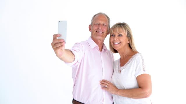 vídeos de stock e filmes b-roll de loving mature couple taking a selfie and having fun - carinhoso