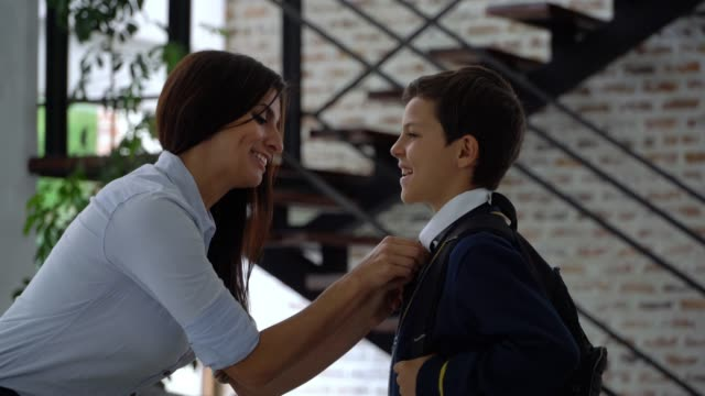 loving mom adjusting necktie of son while talking to him and saying goodbye as he leaves for school - school uniform stock videos & royalty-free footage