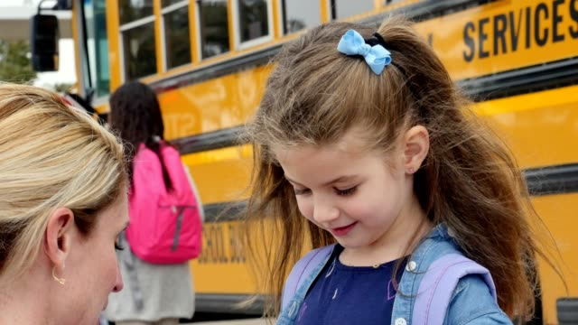 Loving mom gives her give her young daughter advice before the girl boards school bus