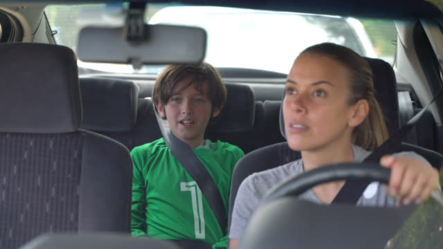 loving mom looking at her son through the rear view mirror while he tells her about the soccer practice - drive ball sports stock videos & royalty-free footage
