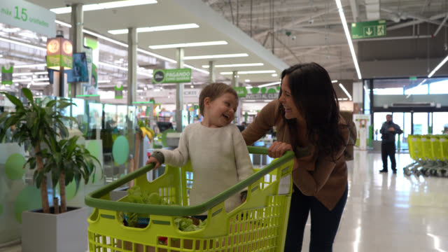 loving mom pushing shopping cart with son inside leaving after buying groceries at the supermarket both talking and smiling - paper bag stock videos & royalty-free footage