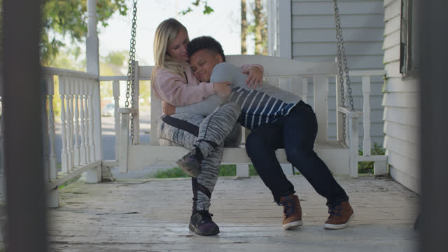 loving mother and son embrace each other as they sit outdoors on a porch swing - 35 39 years stock videos & royalty-free footage