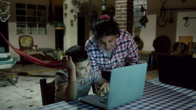 vídeos y material grabado en eventos de stock de madre amorosa ayudando a su hijo e hija mientras trabajan en su tarea usando computadoras portátiles en un hogar rural - hispanoamérica