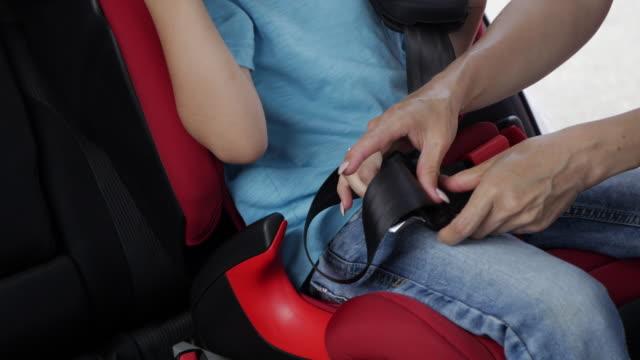 vídeos y material grabado en eventos de stock de amorosa madre ayuda a su hijo para sujetar la correa de asiento de auto - carro blindado