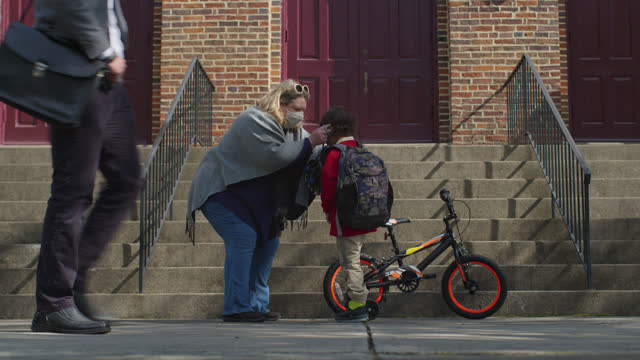 loving mother helps put a protective face mask on her son before he goes to school - protection stock videos & royalty-free footage