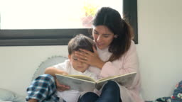 Loving mother kissing her son's head while reading a bedtime story at home