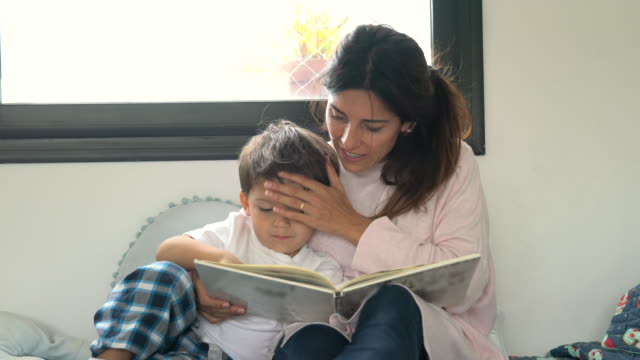 loving mother kissing her son's head while reading a bedtime story at home - family with one child stock videos & royalty-free footage