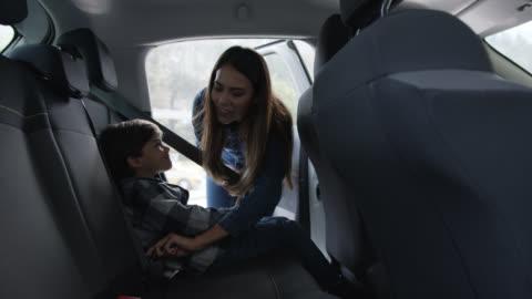 vídeos y material grabado en eventos de stock de madre amorosa asegurando a su hijo en el asiento trasero con el cinturón de seguridad - vehículo terrestre