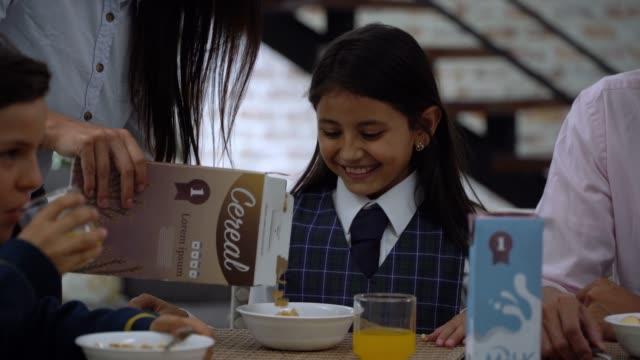 愛する母は、家族の誰もが朝食を食べている間、甘い小さな女の子の笑顔のために穀物を提供します - 制服点の映像素材/bロール