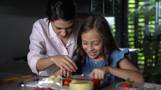 vidéos et rushes de la chère mère enseigne à sa fille comment couper alors qu'elle a l'air excité et concentrés - fille de