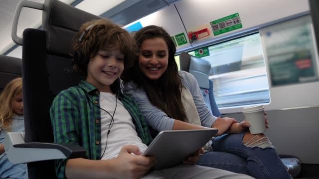 vidéos et rushes de mère aimante regardant son fils jouer avec la tablette numérique ayant l'amusement tout en commutant sur le train - passenger train