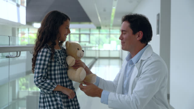 loving paediatrician handing a teddy bear to female patient at the hospital and then both walking away - giving stock videos & royalty-free footage