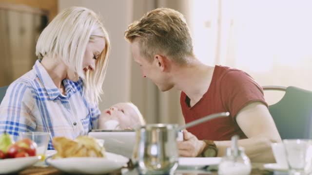 vidéos et rushes de parents ds ms aimant caresser leur bébé tout en prenant son petit déjeuner - ensoleillé