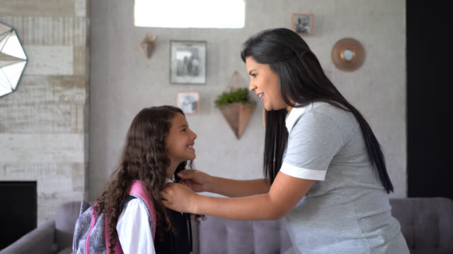 loving pregnant mother helping daughter with her uniform before leaving school both smiling - uniform stock videos & royalty-free footage
