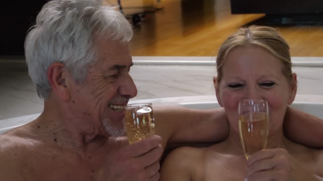 Loving senior couple enjoying champagne in the jacuzzi making a toast smiling very happy