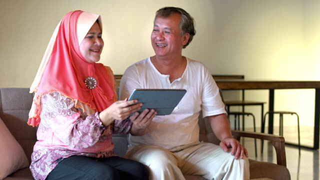 loving senior couple holding digital tablet at home - hijab stock videos & royalty-free footage