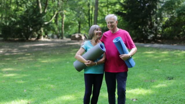 senior liebespaar halten trainingsmatten im park - gymnastikmatte stock-videos und b-roll-filmmaterial