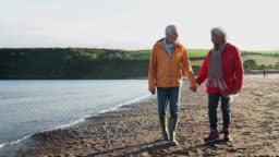 Loving senior couple holding hands walking along shoreline on winter beach vacation - shot in slow motion