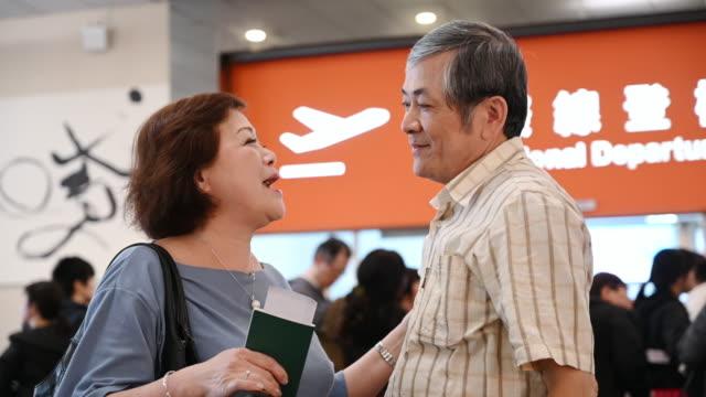 liebevolles seniorenpaar verabschiedet sich und umarmt sich beim flughafen-abflug - auseinander stock-videos und b-roll-filmmaterial