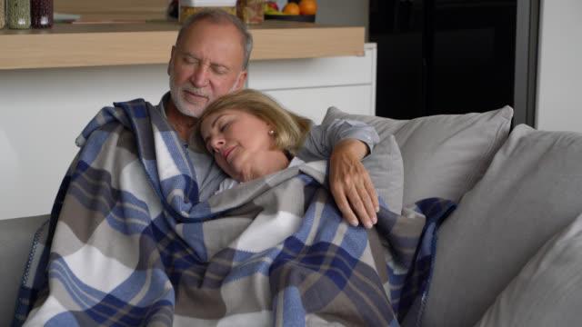 vídeos y material grabado en eventos de stock de ama pareja mayor durmiendo en el sofá con una cubierta en la parte superior buscando muy cómodo - manta ropa de cama