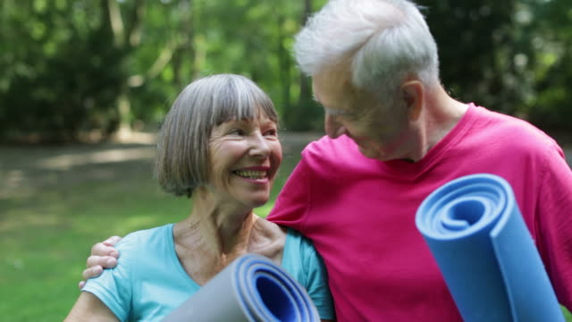 vídeos de stock e filmes b-roll de loving senior couple with exercise mats in park - cuidado com o corpo