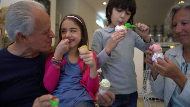vídeos y material grabado en eventos de stock de amante mujer senior mirando muy feliz disfrutando de un café con un hombre irreconocible en una panadería - cuchara de helado