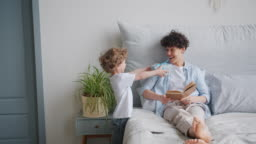 Loving son giving present to mother kissing while girl reading book in bed