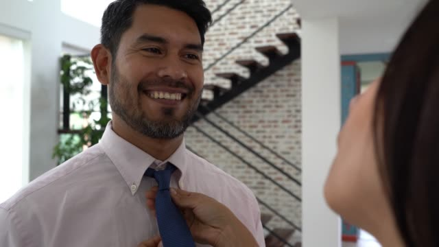 loving wife adjusting necktie while husband talks and smiles - wife stock videos & royalty-free footage