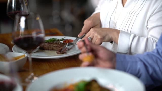 loving woman sharing her meat with partner at a restaurant looking very happy - steak stock videos & royalty-free footage