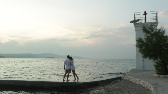 ws loving, young couple embrace and continue to walk by the sea. - ブラック島点の映像素材/bロール