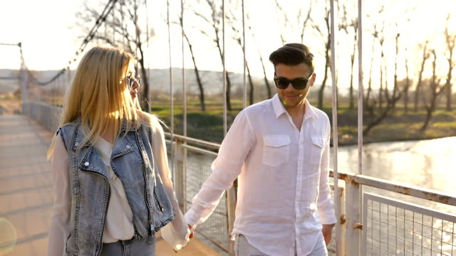 loving young couple on pedestrian bridge - handsome people stock videos & royalty-free footage